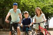 Happy family of three cycling through city — Stock Photo