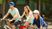 Smiling family of three cycling on city street — Stock Photo