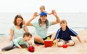 Parents and their children on sand — Stock Photo