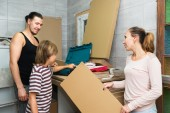 Son helping parents  to unpack boxes — Stock Photo