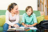 Mother helping teenager with homework — Stock Photo