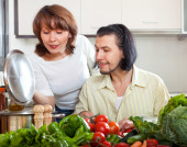 Housewife with man cooking with fresh  vegetables — Stock Photo