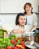 Man and  woman with vegetables in the kitchen — Stock Photo
