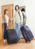 Two tourists with luggage near door  — Stock Photo