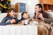 Family of three with cups of tea  in Christmas   — Stock Photo