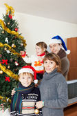 Happy family of four  with  Christmas tree — Stock Photo
