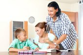 Couple with clever  teenager doing homework   — Stock Photo