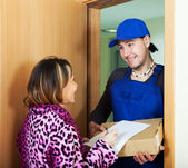 Smiling courier in uniform brought package — Stock Photo