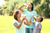 Happy family drinking water — Stock Photo