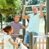 Man with family training on chin-up bar — Stock Photo