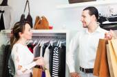 Man and woman with bags at store — Stock Photo
