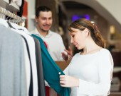 Girl and guy choosing clothes — Stock Photo