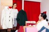 Young couple choosing coat at shop — Foto Stock