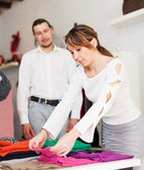Ordinary couple choosing clothes at shop — Stock Photo