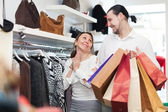 Young couple choosing clothes at boutique — Stock Photo