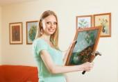 Happy girl hanging art pictures — Stock Photo