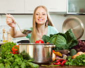 Positive housewife cooking  at home — Stock Photo