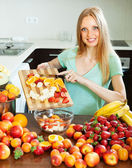 Blonde woman cutting fruits for salad   — Stock Photo