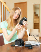Girl unpacking new objective for digital camera — Stockfoto