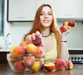 Happy pretty  woman holding peaches   — Stock Photo