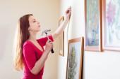 Chica colgando cuadros en marcos — Foto de Stock