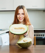 Girl with ripe melon at  kitchen  — Stock Photo