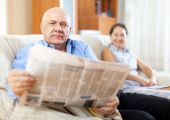 Mature couple together with newspaper — Stock Photo
