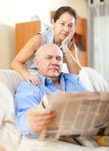 Senior guy with newspaper and mature wife — Stock Photo