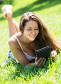 Girl lying on grass with tablet — Stock Photo
