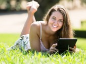 Girl lying on grass with ereader — Stock Photo