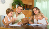 Parents and little daughters with documents — Stock Photo