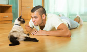 Guy playing with Siamese kitten — Foto Stock