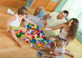 Family of four at home with toys — Stock Photo