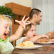 Family of four eating spaghetti — Stock Photo #54982569