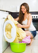 Pretty young woman washing clothes in washer — Stock Photo
