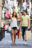 Smiling  young pair with shopping bags at city — Stock Photo