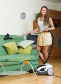 Woman vacuuming living room — Stock Photo