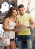 Two friends with map in the street — Stock Photo