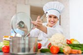L cook  in toque works with ladle  — Stock Photo