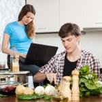 Man preparing food while woman looking at laptop — Stock Photo #54992691