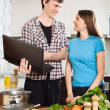 Smiling man shows the new recipe to girl — Stock Photo #54992771