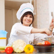 Cook with ladle adds salt into soup pan — Stock Photo #54994857