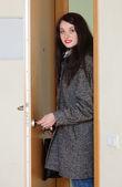 Woman in coat unlocking the door   — Stock Photo