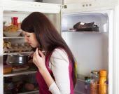 Brunnette woman holding foul food near refrigerator   — Stock Photo