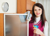 Smiling brunette girl cleaning  glass   — Stock Photo