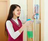 Happy brunette woman cleaning  mirror   — Stock Photo
