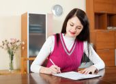 Smiling brunette woman filling in financial documents   — Stock Photo