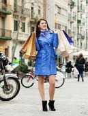 Usmívající se žena v plášti s nákupy — Stock fotografie