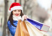 Happy woman in Santa hat with purchases — Stock Photo