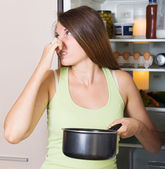 Woman holding foul food — Stock Photo